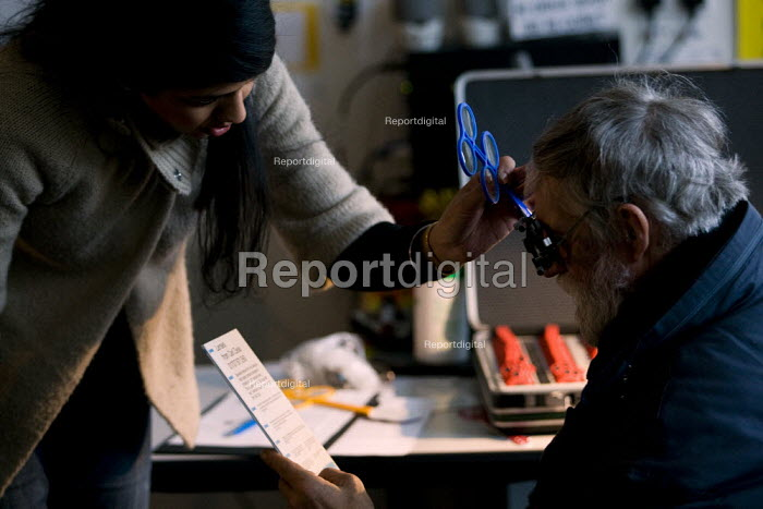 Volunteer optician tests a homeless man. Crisis day centre opens at Bermondsey City of London Academy. Providing homeless and vulnerably housed people with a range of services, food and shelter. - Jess Hurd - 2009-12-23