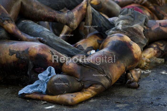 Dead bodies are shovelled into a truck. Haiti earthquake. - Jess Hurd - 2010-01-18