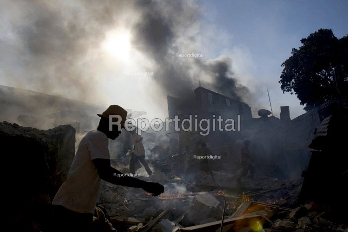 Haitians salvage food and goods necessary for survival from burning buildings. Haiti earthquake. Port-au-Prince. Haiti. - Jess Hurd - 2010-01-18