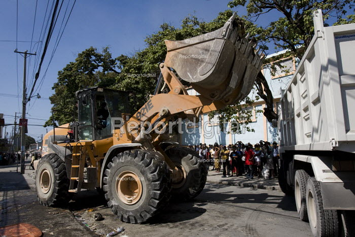 Dead bodies piled on the street are shovelled into a truck. Haiti earthquake. - Jess Hurd - 2010-01-18