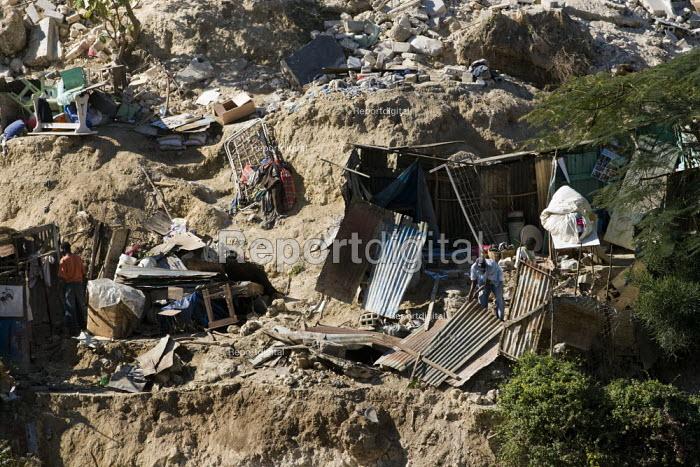 A man picking his way through the remains. Devastated hillside communities. Port-au-Prince, Haiti earthquake. - Jess Hurd - 2010-01-18