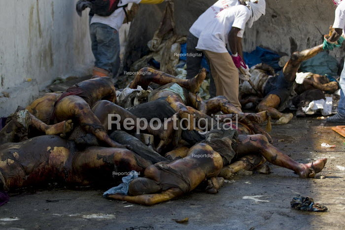 Dead bodies left on the street are shovelled into a truck. Haiti earthquake. - Jess Hurd - 2010-01-18