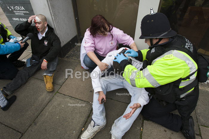EDL supporters receive medical help from paramedics after rioting with police and are interviewed by the media. English Defence League protest. Leicester. - Jess Hurd - 2010-10-09