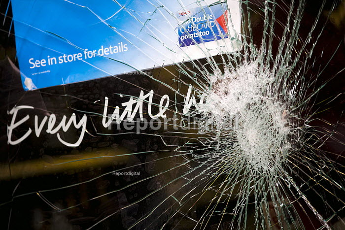 Smashed window of Tesco - Every little helps campaign slogan for the loyalty card Clubcard, suggesting low prices, following the fatal police shooting of Mark Duggan, 29, was killed by police in Tottenham. South London. - Jess Hurd - 2011-08-10