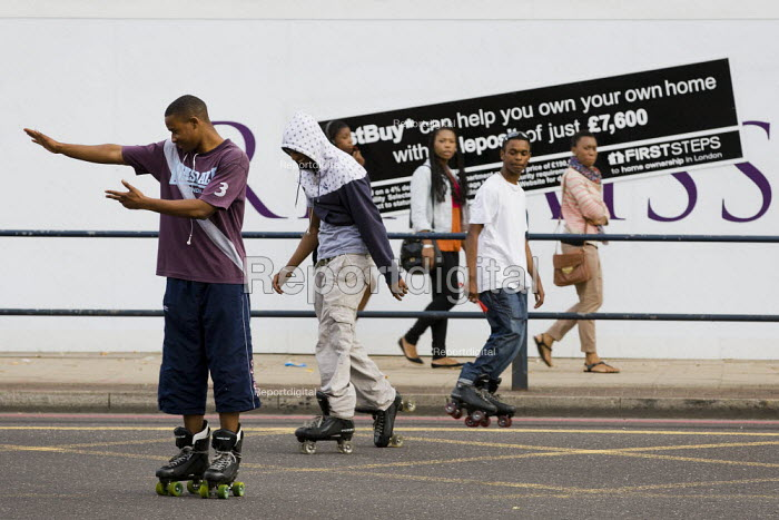 Young black men rollerskate past an advert for owning your own home. Lewisham, South London. - Jess Hurd - 2011-08-10