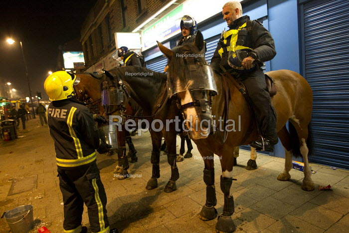 A Firefighter gives Police horses water. Riots in Tottenham. Riot police clashed with hundreds of rioters after the fatal shooting of Mark Duggan, 29, who was killed by police on Thursday. North London. - Jess Hurd - 2011-08-06