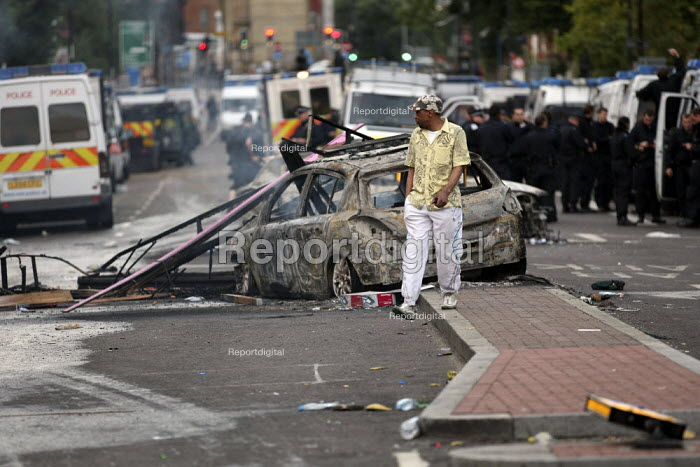 Local walks past a burnt out police cars. Riots in Tottenham. Riot police clashed with hundreds of rioters after the fatal shooting of Mark Duggan, 29, who was killed by police on Thursday. North London. - Jess Hurd - 2011-08-07