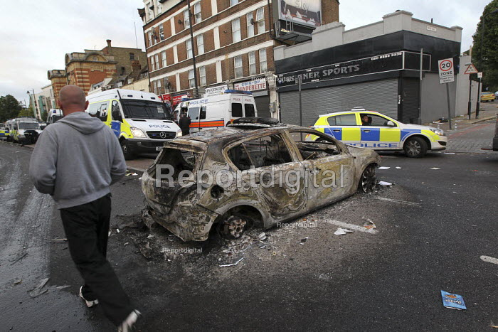 A local walks past a burnt out police car. Riots in Tottenham. Riot police clashed with hundreds of rioters after the fatal shooting of Mark Duggan, 29, who was killed by police on Thursday. North London. - Jess Hurd - 2011-08-06