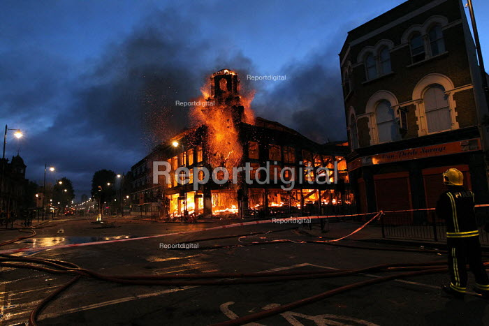 """Carpet shop burns as violence erupts in Tottenham after a protest demanding """"justice"""" over a fatal police shooting. Riot police clashed with hundreds of rioters after Mark Duggan, 29, a father of four, was killed on Thursday. North London. - Jess Hurd - 2007-07-16"""