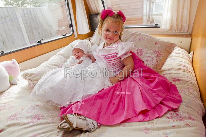 Rihanna and her 12 day old sister, Vivienne in their caravan on the day of her baptism. Dale Farm traveller site. Basildon, Essex. - Jess Hurd - 2011-09-11