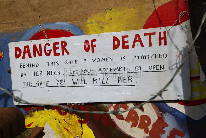 Danger of Death. Warning sign on a door: Behind this gate a woman is attached by her neck. Travellers from Dale Farm facing eviction by Basildon Council. Essex. - Jess Hurd - 2011-09-23