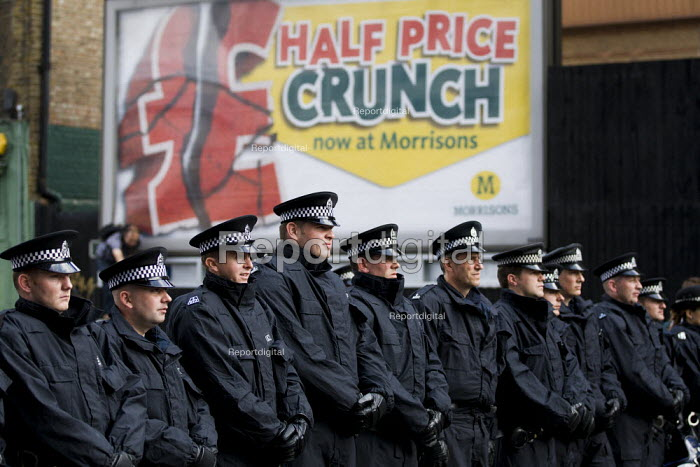 Police infront of an advert for Morrisons supermarket - half price crunch. English Defence League attempt to march in Tower Hamlets is stopped by a state ban and the mobalisation of local people by Unite Against Fascism. East London. - Jess Hurd - 2011-09-03