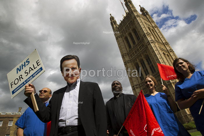 On the eve of the third reading in parliament of the Health and Social Care bill NHS workers in medical scrubs and a David Cameron mask hold an NHS For Sale estate agents board to symbolise the privatisation of the NHS. Westminster, London. - Jess Hurd - 2011-09-05