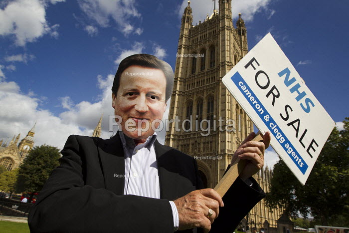 On the eve of the third reading in parliament of the Health and Social Care bill NHS workers in David Cameron mask hold an NHS For Sale estate agents board to symbolise the privatisation of the NHS. Westminster, London. - Jess Hurd - 2011-09-05