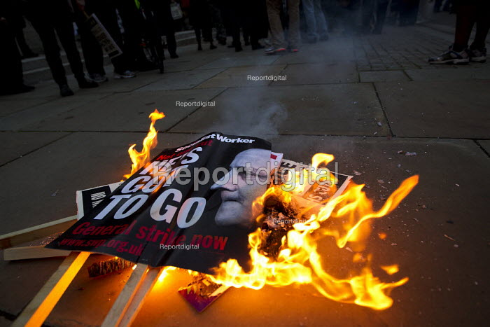Burning Socialist Worker placard saying David Cameron - He's Got to Go. Candlelit vigil in Westminster as the Health and Social Care Bill is voted on in the Commons. NHS staff burning placards, London. - Jess Hurd - 2011-09-07