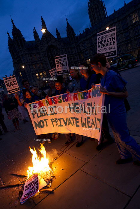 Public Health not Private Wealth banner. Candlelit vigil in Westminster as the Health and Social Care Bill is voted on in the Commons. NHS staff burning placards, London. - Jess Hurd - 2011-09-07