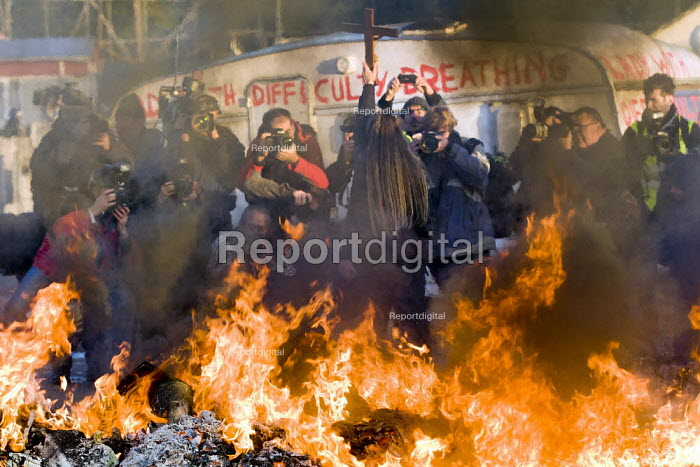 A pack of press photographers posing a photograph with a traveller and a crucifix infront of a burning barricade. Dale Farm eviction, Basildon. London. - Jess Hurd - 2011-10-19