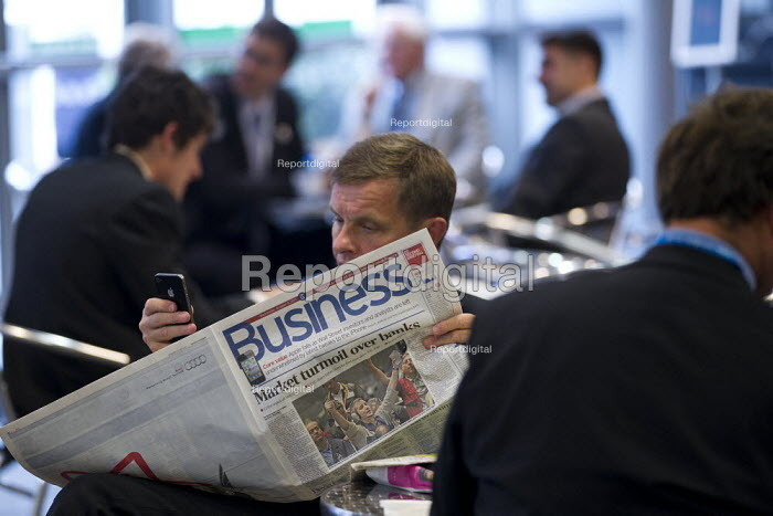 Delegate with mobile phone and Business headline Market in Turmoil Over Banks. Conservative Party Conference, Manchester, 2011. - Jess Hurd - 2011-10-05