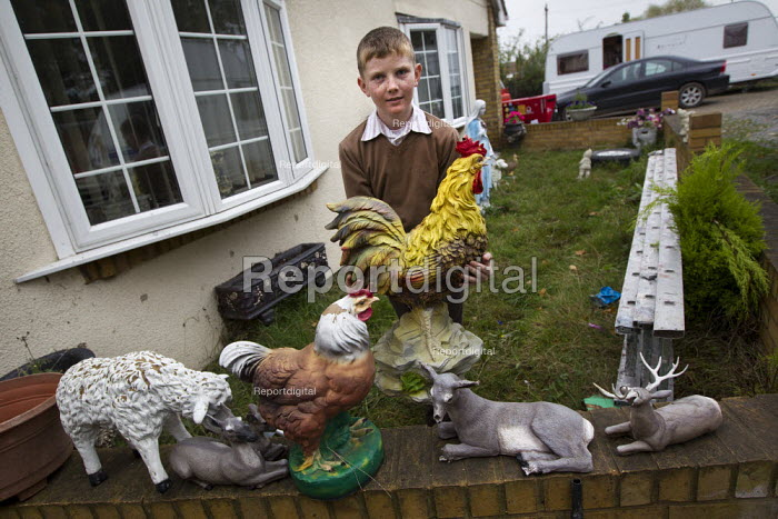 A young traveller helps his mother clean the garden ornaments on one of the legal plots left on Dale Farm. Constant & Co bailiffs and contractors bulldoze the plots at Dale Farm after Basildon Council evicted most of the traveller residents. Essex. - Jess Hurd - 2011-11-07