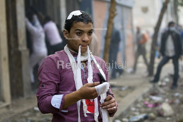 Protester bandages his own wounds on the front line. Uprising against the military junta. Al-Tahrir (Liberation Square), Cairo, Egypt - Jess Hurd - 2011-11-23