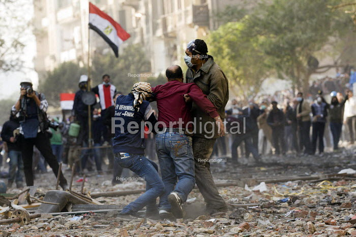 Fighting on Mohamed Mahmoud, injured are carried away. Uprising against the military junta. Al-Tahrir (Liberation Square), Cairo, Egypt - Jess Hurd - 2011-11-23