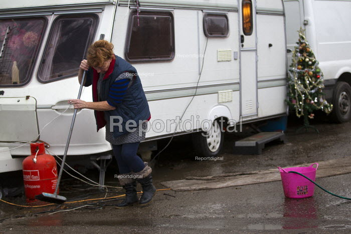 Maime Slattery tries to clear the comtaminated water from the septic tank broken by bailiffs. Dale Farm traveller site post eviction. Travellers report that the site and water supply is conaminated, after Basildon council bailiffs bulldozed the site, removed the hardcore and built levees and trenches. Parents claim that many of the children are becoming sick. Essex. - Jess Hurd - 2011-12-21