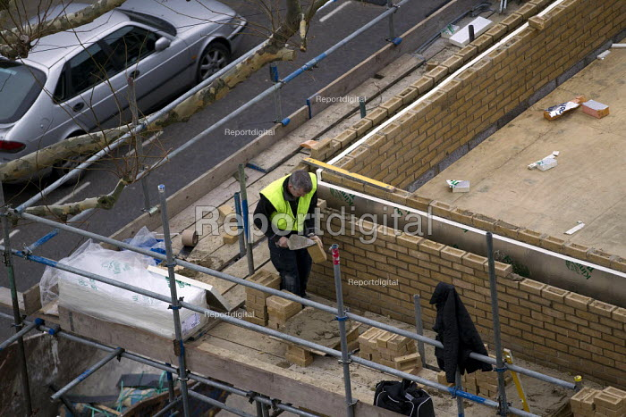 Brick layer constructing the walls of a social housing project in Tower Hamlets, East London. - Jess Hurd - 2012-01-11