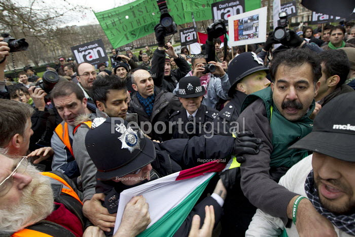 Stop the war before it starts. Iranian nationalists are escorted out of the protest by stewards and police. Stop the War demonstration against an attack on Iran. US Embassy, London. - Jess Hurd - 2012-01-29