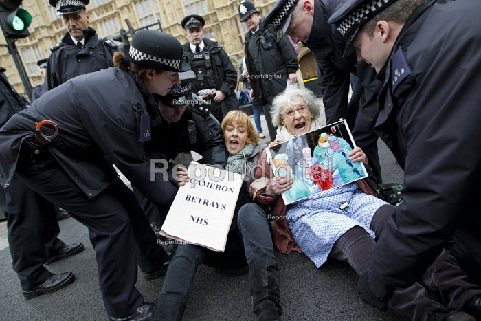 Police carry away UK Uncut protester 81 year old Shirley Murgraff who blocked the road outside the House of Lords against the NHS Bill. Steve Bell, Guardian cartoon placard and Cameron Betrays NHS. Westminster, London. - Jess Hurd - 2012-02-27