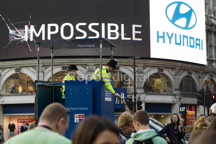 Police officer confiscates a can of alcohol in a controlled drinking zone. Mobile police watchtower. Operation Trafalgar launched in West End London. Increased, visible policing is designed to tackle crime, disorder and anti-social behaviour. Piccadilly Circus. - Jess Hurd - 2012-03-29