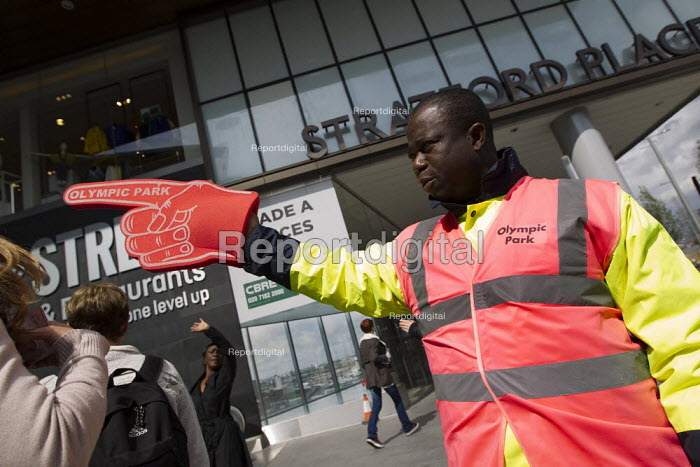 Olympic Park worker directing people to the venue through Westfield Shopping Centre. Stratford, Newham. East London. - Jess Hurd - 2012-04-22