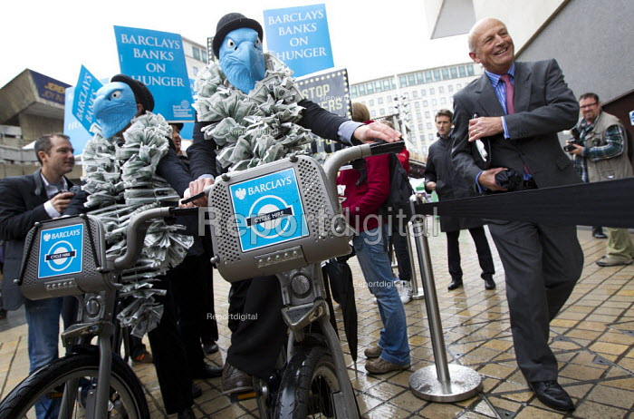 Campaigners from the World Development Movement protest at Barclays AGM, exposing Barclays Capitals role in food speculation which WDM say increases global food prices leaving millions facing hunger and malnutrition. Two suited, blue masked Barclays eagles on Barclays bikes join protestors holding placards reading Barclays banks on hunger. South Bank, London. Campaigners from the World Development Movement protest at Barclays AGM, exposing the role of Barclays Capital in food speculation which WDM say increases global food prices leaving millions facing hunger and malnutrition. Two suited, blue masked Barclays eagles on Barclays bikes join protestors holding placards reading Barclays banks on hunger. South Bank, London - Jess Hurd - 2012-04-27