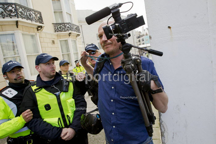 Video journalist Jason N. Parkinson (showing his NUJ press card), is pushed through a cordon after being assaulted by an EDL supporter and a police officer from Essex police. English Defence League disrupt a UK Uncut anti austerity, anti monarchy street party, Diamond Jubilee weekend, Brighton. - Jess Hurd - 2012-06-02