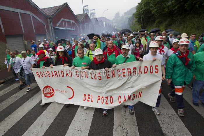 Miners march past Pozo de Soton coal mine after fighting between police and miners to keep control of the pit. The miners have been on strike since the government announced cuts to mining subsidies due to austerity cuts which will mean an end to mining. Asturias. Northern Spain. - Jess Hurd - 2012-06-16