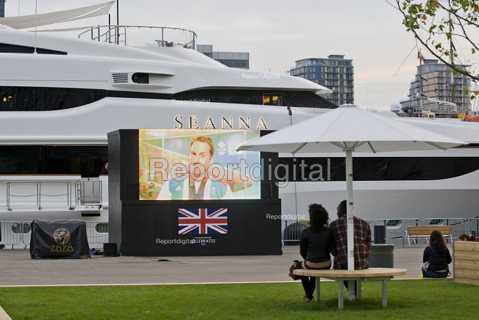 A handful of spectators watch a big screen TV the end of the athletics in a prepared spectator area where the super-yatchs are moored. The Seanna, is one of the Super-yatchs moored at Canary Wharf for the London 2012 Olympics. Tower Hamlets, East London. The Seanna is a 213-foot boat that is being chartered out to super-wealthy visitors for the Games and the duration of the summer for 294,000 a week. - Jess Hurd - 2012-08-11
