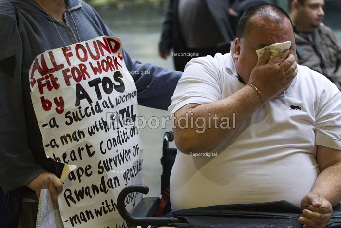 Disabled protesters lay a coffin outside Atos HQ to represent the people who have committed suicide after having their benefits cut. Opening day of the Paralympics. Euston, London. - Jess Hurd - 2012-08-29