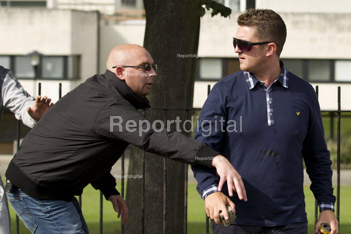 Tommy Robinson, real name Stephen Yaxley-Lennon, leader of the EDL as one of his security guards tries to take a brick off him. A march and rally by the English Defence League is stopped by thousands of local anti-fascist protesters We Are Waltham Forest, who blocked the march by sitting in the road. Walthamstow. - Jess Hurd - 2012-09-01