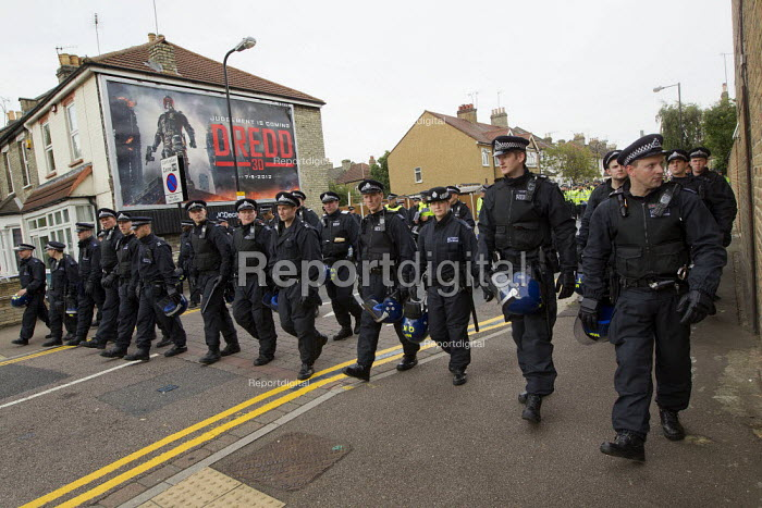 EDL march back to the station. Police pass an advertisement for the action film Dredd 3D Judgement is coming, set in a future dystopia. A march and rally by the English Defence League is stopped by thousands of local anti-fascist protesters We Are Waltham Forest, who blocked the march by sitting in the road. Walthamstow. - Jess Hurd - 2012-09-01
