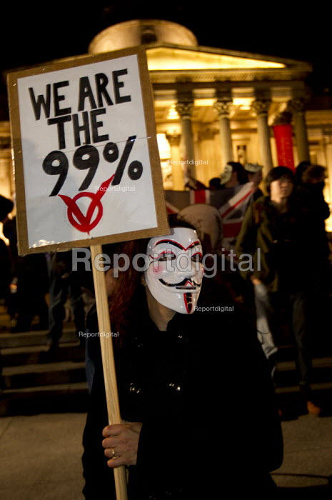 We are the 99% placard. London joins a worldwide day of protests and cyber attacks against governments, banks and security firms has been launched by Hacker collective Anonymous to mark Guy Fawkes Day. March from Trafalgar Square to Westminster Parliament. - Jess Hurd - 2012-11-05