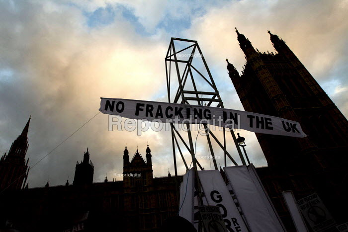 Get Fracktious. National Climate March against global warming and fracking. Campaigners erect a fracking rig outside Westminster Parliament. London. - Jess Hurd - 2012-12-01