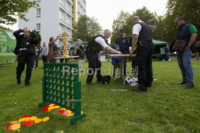 Police playing giant Jenga, Connect 4 and Carrom. Summer Night Lights, a pilot summer violence reduction programme originally launched in Los Angeles to addresses peak offending in anti social hotspots with play activities for all ages. Funded by Tower Hamlets Council and the Met Police. East London. - Jess Hurd - 2014-08-21