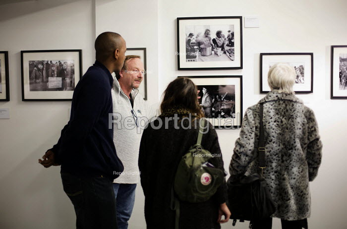 Photographer John Harris talking to visitors about his images at the, Still The Enemy Within, miners strike exhibition at Rich Mix, London. - Jess Hurd - 2014-12-05