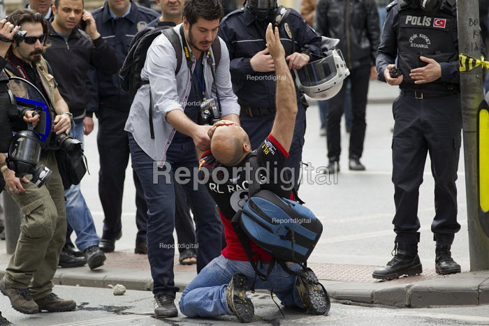 Injured journalist is helped and photographed by his colleagues. Turkish police surround Taksim Square to prevent May Day marches. Istanbul, Turkey. - Jess Hurd - 2014-05-01