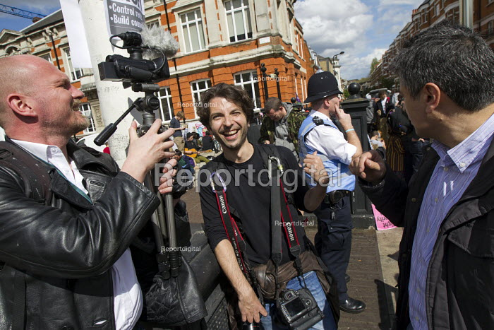 Police Liaison Officer moves closer to listen in on journalists conversation. Protest to Reclaim Brixton. Against gentrification and regeneration that does not benefit the existing community. South London. - Jess Hurd - 2015-04-25