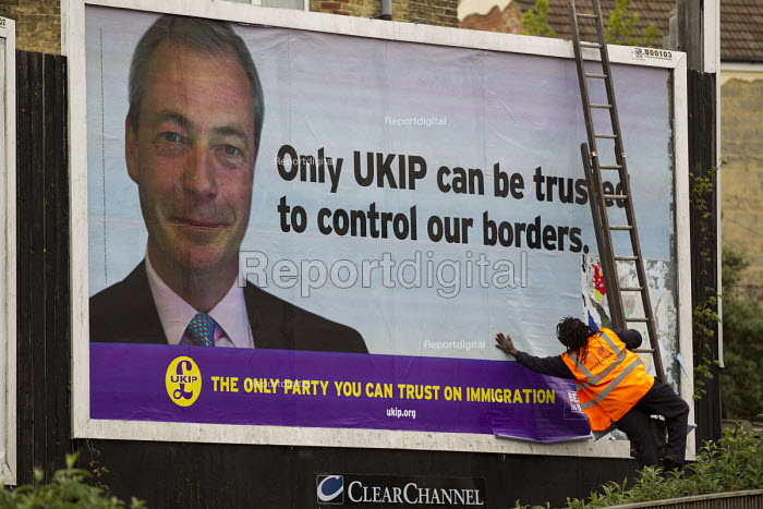 Black worker pasting a UKIP election immigration poster Only UKIP can be trusted to control our boarders for Nigel Farage in Thanet. - Jess Hurd - 2015-05-02