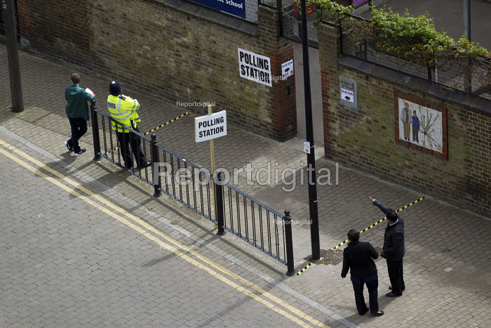 Police tape marks the proscribed area, preventing promotion or distribution of campaign literature by Labour Party supporters outside a Tower Hamlets polling station. General Election. East London. - Jess Hurd - 2015-05-07