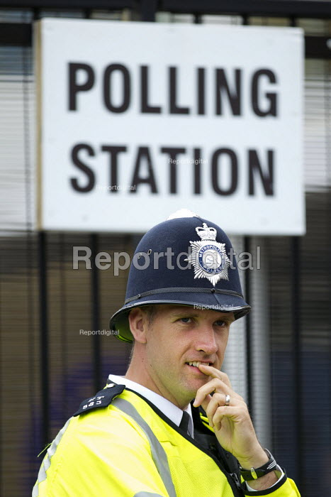 Police officer on duty at a Tower Hamlets Polling Station. General Election. East London. - Jess Hurd - 2015-05-07