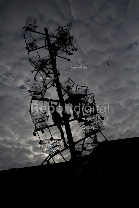 Children climb on a sculpture of shopping trolleys called DNA DL90 on a site opposite an Amazon warehouse. The artwork by Abigail Fallis is part of The Line: a new modern art walk. Newham. East London. Commissoned by the supermarket Somerfield to create an artwork for the Muscular Dystrophy charity. - Jess Hurd - 2015-05-23