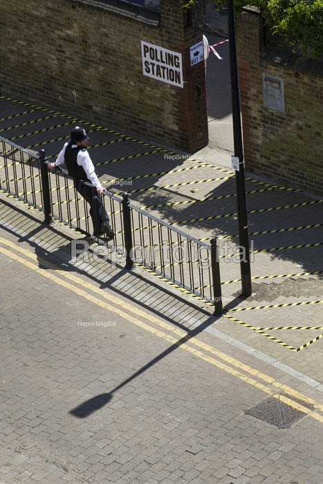 Policing a restricted area around a Polling Station, Tower Hamlets vote in a re-run of the mayor elections after corruption allegations against Lutfur Rahman. East London. - Jess Hurd - 2015-06-11