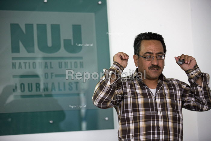 Nablus based Reuters photojournalist Abed Qusini speaks at the NUJ about his work and the safety of journalists. He shows the remote control for his hearing aid after being hit with a concussion grenade. London. - Jess Hurd - 2015-06-23